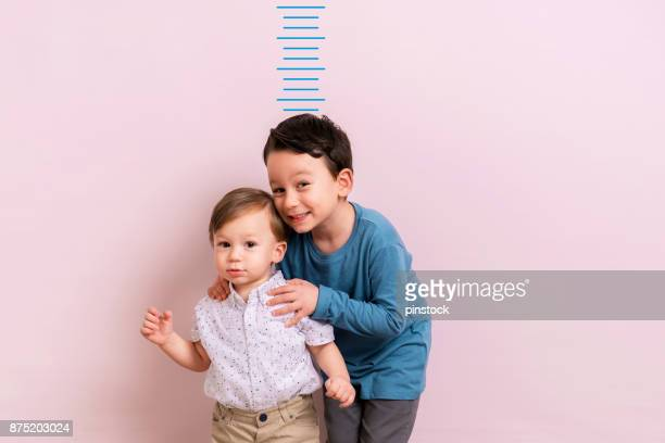 kind, seine höhe zu messen - bruder stock-fotos und bilder