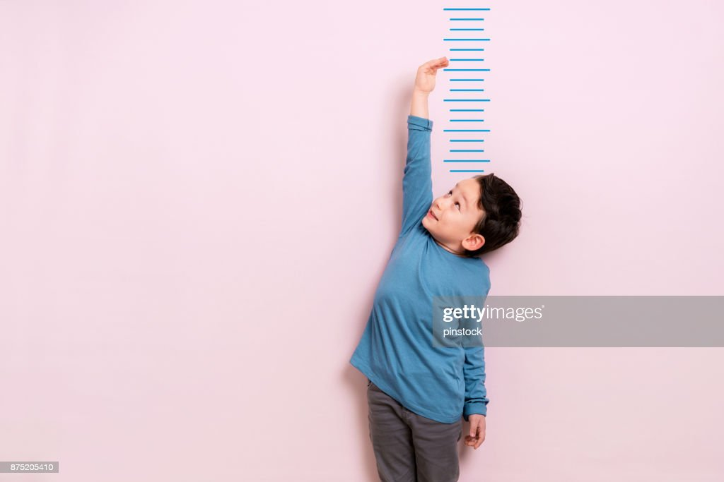 Child measuring his height : Stock Photo