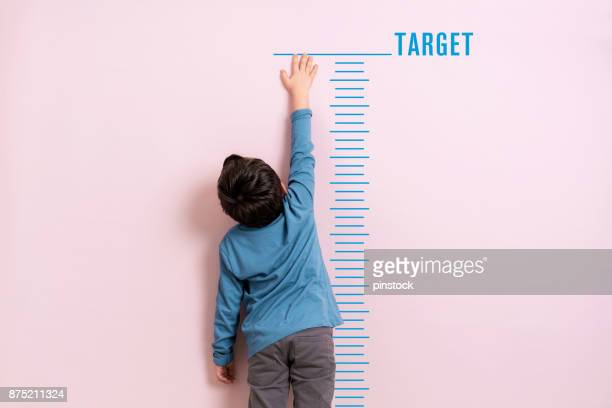 child measuring his height - medir imagens e fotografias de stock