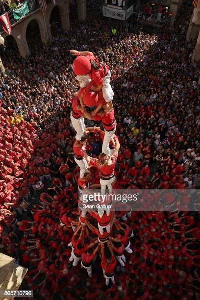 A child member called the 'enxaneta' raises her hand to signal she has climbed to the summit of her team's human tower and will begin her descent...