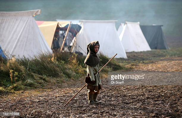 A child member of an historical reenactment group dressed as a Norman soldier stands in his encampment before the annual reenactment of the Battle of...