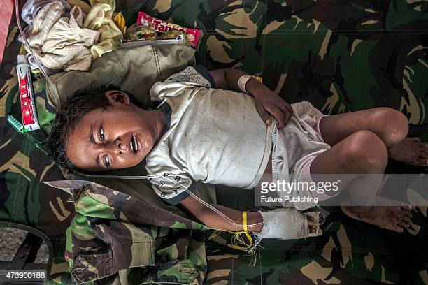 A child migrant from Myanmar cries as he gets medical attention at a makeshift camp on May 18 2015 in Kuala Langsa Indonesia Malaysia said on Sunday...