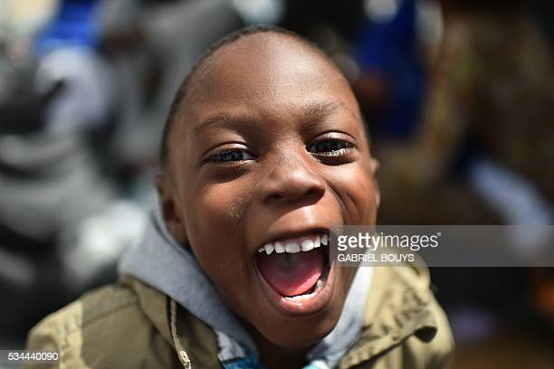 A child migrant laughs prior to leave rescue ship 'Aquarius' as more than 380 migrants arrive in the port of Cagliari Sardinia on May 26 two days...