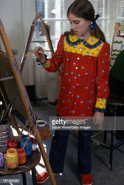 A child model in a red and yellow print smock jeans and red clogs stands paints at an easel in a school art room May 1972 The photo was taken as part...