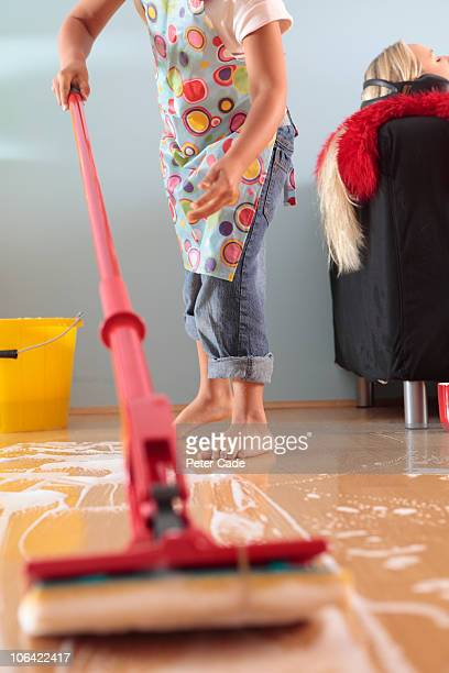 child mopping floor, woman relaxing on sofa