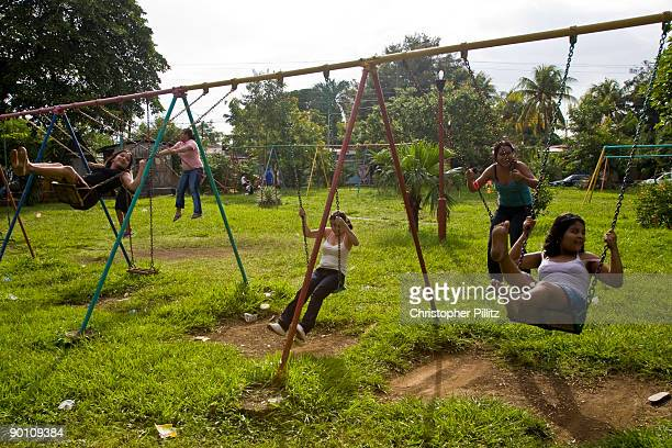 'Child mothers' take a moment to return to what their childhoods should be about playing on swings in a Managua neighbourhood whilst their babies are...