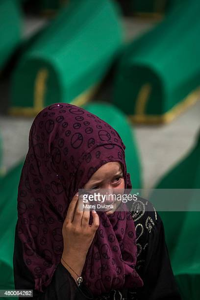 Child mourns over a coffin among 136 coffins of victims of the 1995 Srebrenica massacre in the hall at the Potocari cemetery and memorial near...