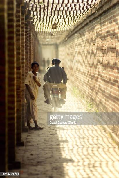 Child moves to the side just in time to avoid being hit by the Police bike. His smile is victorious. This is the ancient passage that leads to Mughal...