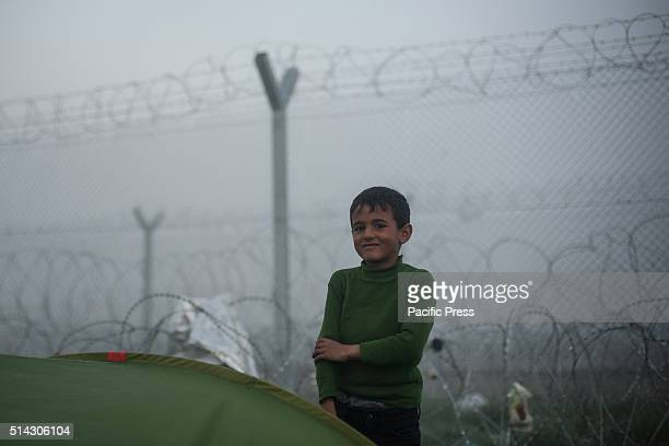 A child near the barbed wire in the camp of Idomeni on the border between Geece and Macedonia Migrants at camp of Idomeni in Greece waiting to get...