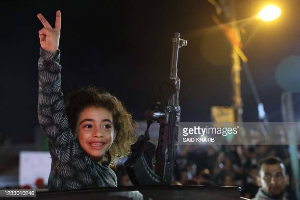 Child next to an automatic rifle flashes the V-sign for victory as people celebrates the ceasefire brokered by Egypt between Israel and the ruling...