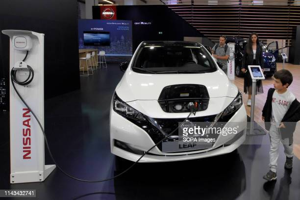 A child observes how the LEAF electric vehicle of the Nissan brand is recharged at the Automobile Trade Fair 2019 in Barcelona