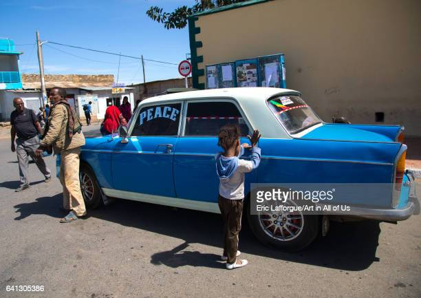Child oeping the door of an old peugeot 404 taxi on January 13 2017 in Harar Ethiopia