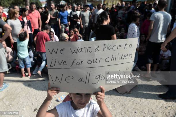 A child of a migrant or refugee who lives in a camp in a suburb west of the northern city of Thessaloniki hold up a placard as the camp inhabitants...