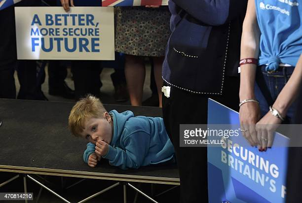 A child of a party activist waits for Britain's Prime Minister and leader of the Conservative Party David Cameron to deliver a speech during a UK...