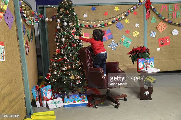 A child of an immigrant family takes over Santa's chair at a Family Night Christmas party at a community immigrant center on December 16 2016 in...
