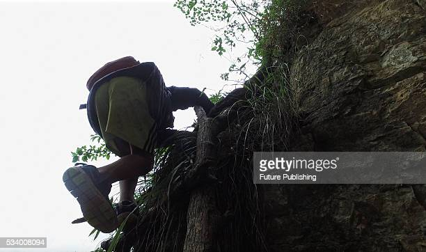A child of Atule'er Village climbs a cliff on way home in Zhaojue county in southwest China's Sichuan province on May 14 2016 in Zhaojue China There...