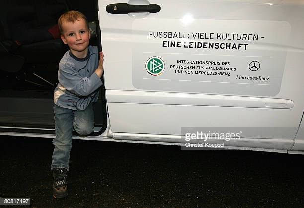 A child of the Gallus quarter poses in front of the Mercedes Transporter Vito after the prize giving of the integration prize at the Mercedes Benz...