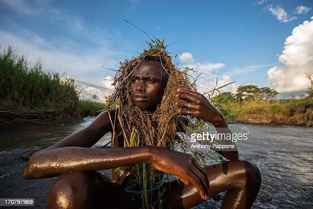 CONTENT] child of the surma tribe with decorated plants in head on the river Kibish ethiopia