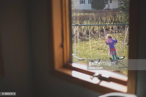 Child on a backyard Swing Set