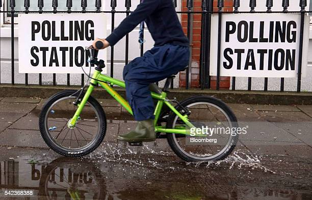 A child on a bicycle rides through a puddle as he passes signs for a polling station in the European Union referendum hanging on the railings outside...