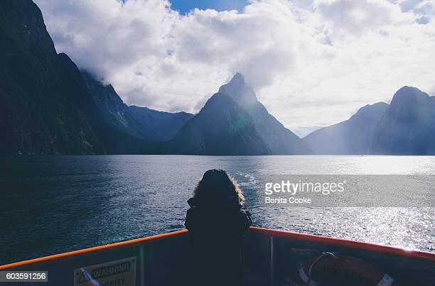 child on a boat, taking a photo of mitre peak, in milford sound - fähre stock-fotos und bilder