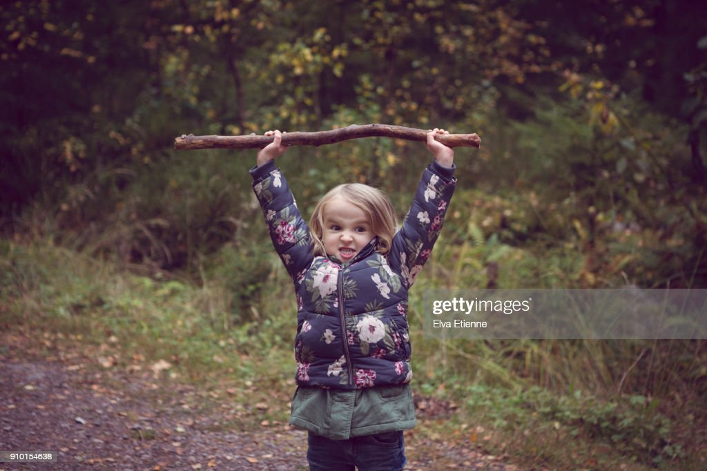 Child on a forest path, holding a big stick above her head : Stock Photo