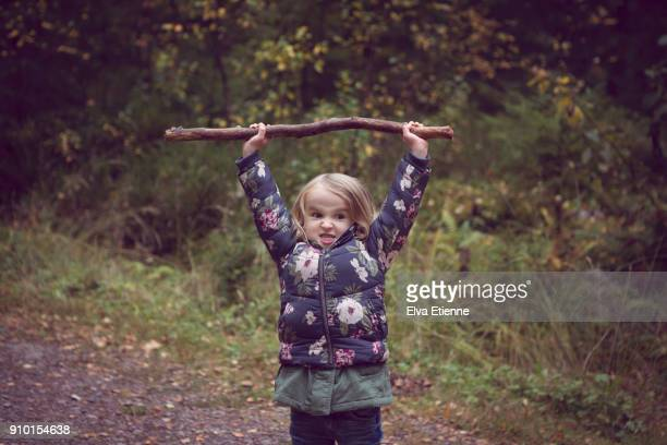 Child on a forest path, holding a big stick above her head
