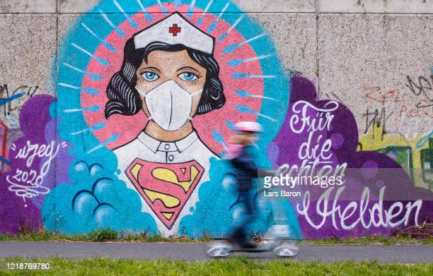 Child on a scooter rides past street art painted by artist Kai 'Uzey' Wohlgemuth featuring a nurse as Superwoman on April 14, 2020 in Hamm, Germany....