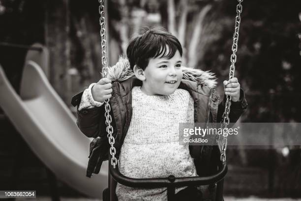 Child on a swing in a winter morning (black and white)