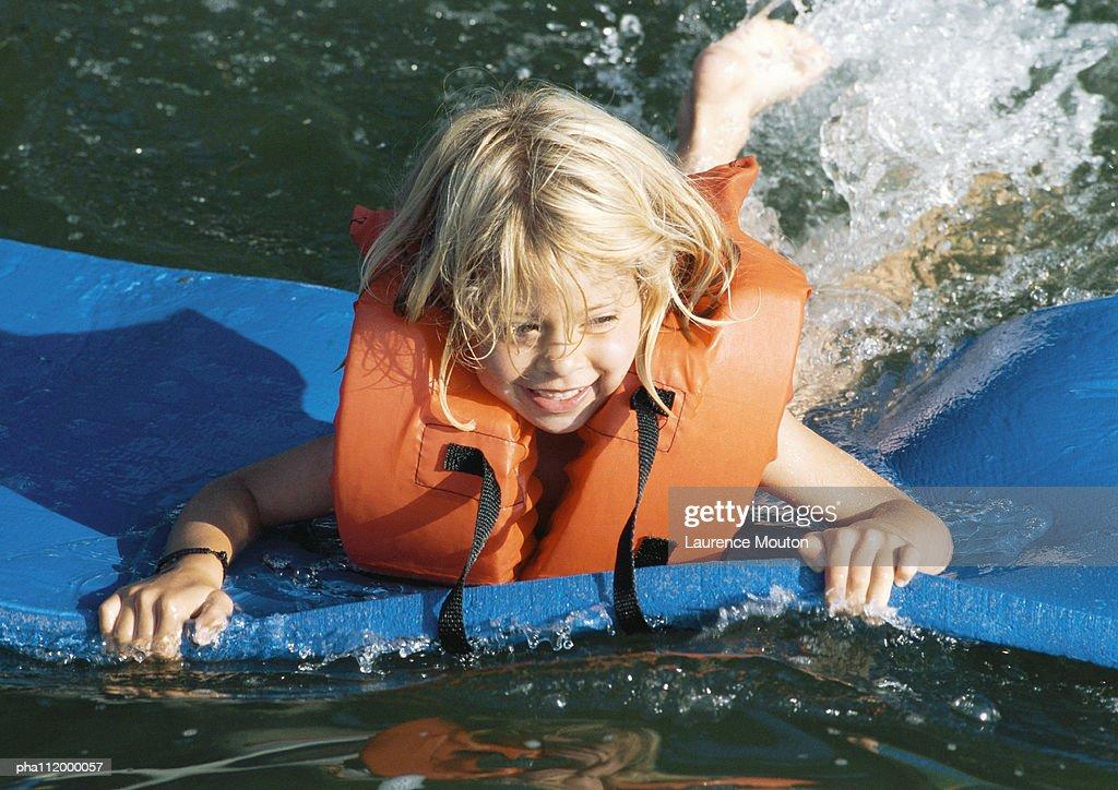 Child on foam board, floating on water : Stockfoto