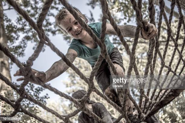 child on mud run obstacle course - obstacle course stock pictures, royalty-free photos & images