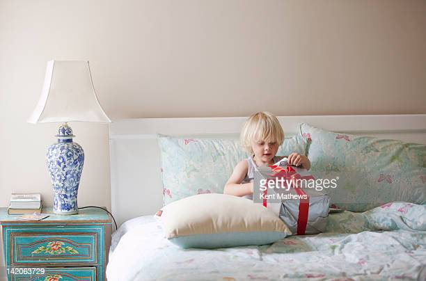 child on parents bed opening present