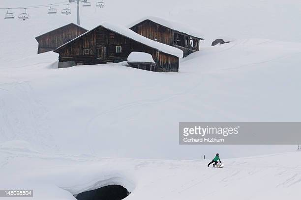 Child on sledge below log cabins on snowy hill