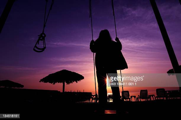 Child on swing at dusk