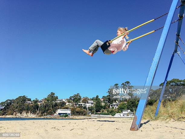 Child on swing at the beach on summer day