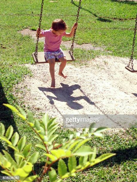 Child on the bench watching her shadow