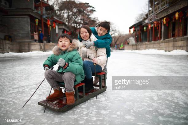 child on the lake freezes to enjoy sledding, ice skate, ice bike at summer palace in beijing in winter, - china east asia stock pictures, royalty-free photos & images