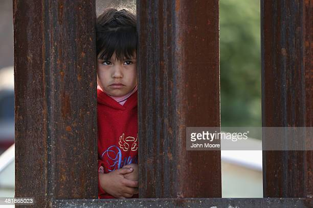 A child on the Mexican side of the USMexico border fence looks into Arizona during a special 'Mass on the Border' on April 1 2014 in Nogales Arizona...