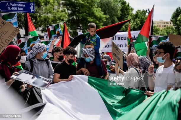 Child on the shoulders of his father holds a Palestinian flag while protesters sing songs of support for Palestine and against Israel in Madrid,...