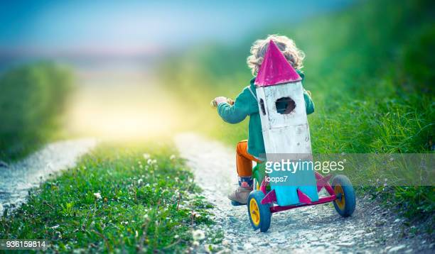child on tricycle carrying a toy space rocket - joy stock pictures, royalty-free photos & images