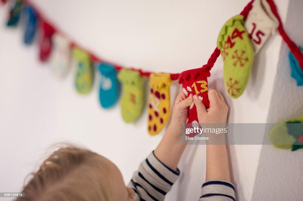 Child opening advent calendar : Stock Photo