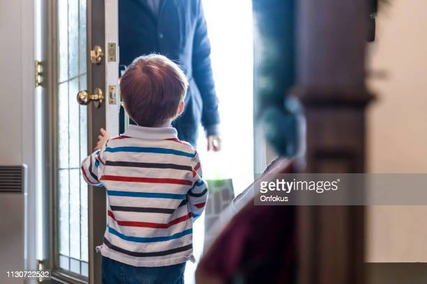 child opening door to father after day of work or delivery person - returning stock pictures, royalty-free photos & images