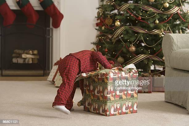 Child opening present near christmas tree