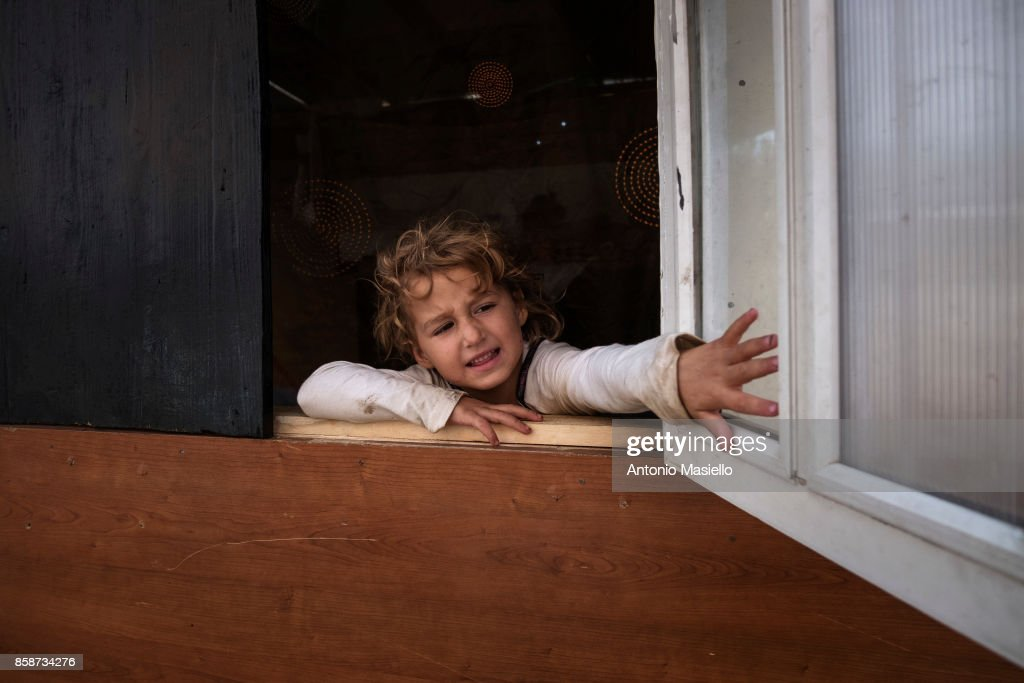 A child opens the window of their room in an occupied building on October 4, 2017 in Rome, Italy. For the last 5 years, hundreds of people, including Italians, Roma and refugees, including around 35 children, have lived in an occupied building on the suburbs of Rome without electricity or a toilet and surrounded by refuse.