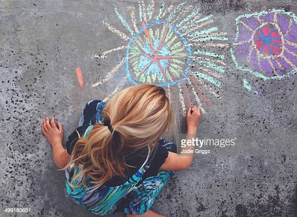Child outside drawing with chalk on concrete