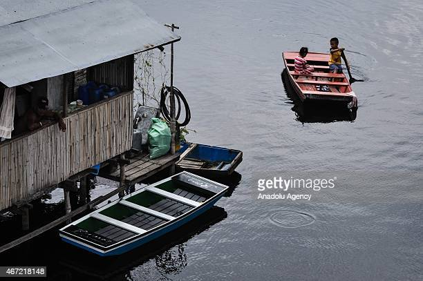 A child paddles a boat inside the submerged residential compund at Artex in Malabon City North of Manila on Sunday Today marks the celebration of the...
