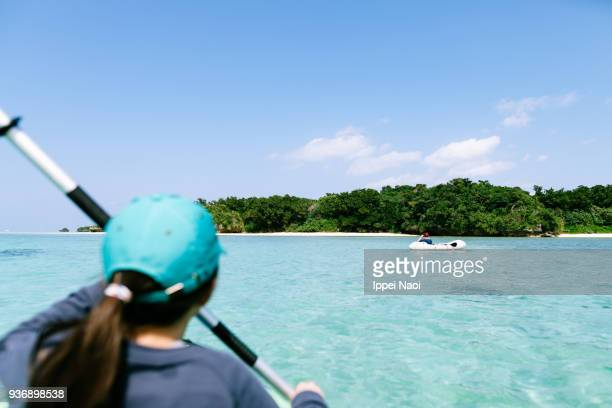 Child paddling kayak on clear tropical lagoon, Ishigaki Island, Okinawa, Japan