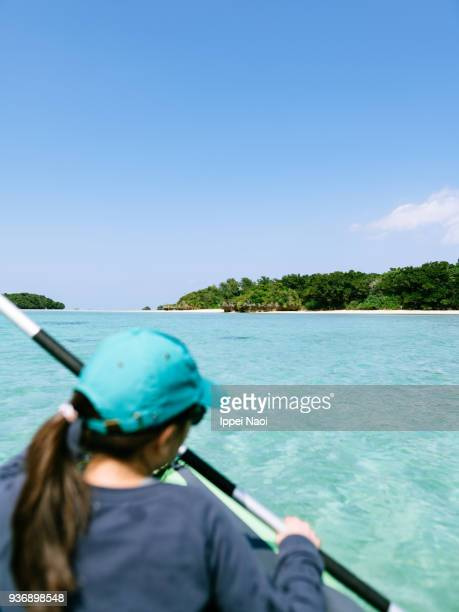 Child paddling kayak on clear tropical water, Ishigaki Island, Japan