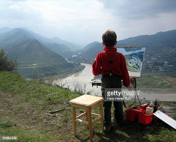 Child painting a Caucasus landscape
