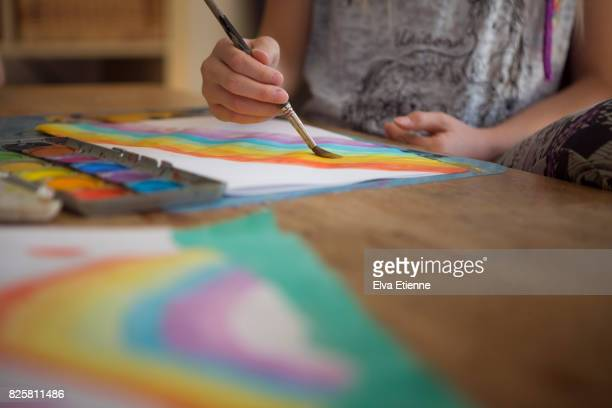 Child painting a picture of a rainbow